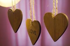 Les coeurs en bois de jour de valentines avec le mot aiment sur le fond rose Photo libre de droits