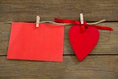 Les coeurs et l'enveloppe rouges avec le tissu chevillent accrocher sur la corde Photo stock