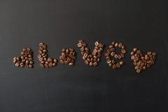 Les coeurs et le mot aiment écrit par des grains de café Images stock