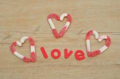 Les coeurs fabriqués à partir de des cannes de sucrerie avec le mot aiment Photo stock