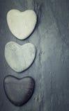 Les coeurs gris, noirs, blancs de zen ont formé la roche sur un fond de tuile Image stock