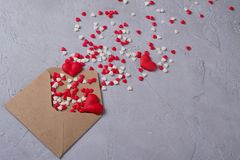 Les coeurs multicolores de sucrerie de sucre de bonbons volent hors de l'enveloppe postale de papier de métier Concept heureux de Image stock