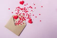 Les coeurs multicolores de sucrerie de sucre de bonbons volent hors de l'enveloppe postale de papier de métier Dayconcept heureux Images libres de droits