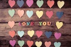 Les coeurs multicolores sur le fond et le texte en bois vous aiment pour la célébration de Saint Valentin et d'amour photos libres de droits