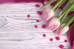 Les coeurs pourpres avec les tulipes roses sur le blanc ont peint le fond en bois blanc rustique Jour de Valentine Images stock