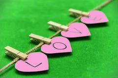 Les coeurs roses de plan rapproché avec le mot aiment dessus au vert d'herbe moite Image libre de droits