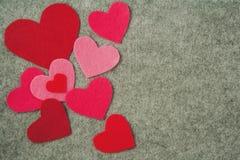 Les coeurs roses et rouges sur le gris ont senti le fond Photo stock