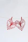 Les coeurs rouges avec des modèles ont coupé du papier sur un fond clair Images libres de droits