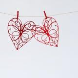 Les coeurs rouges avec des modèles ont coupé du papier sur un fond clair Photos libres de droits