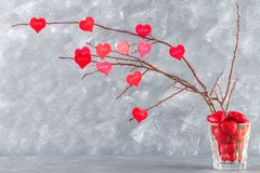 Les coeurs rouges avec un amour d'inscription accrochent sur des branches sur un fond concret gris Arbre d'amour Le concept de la Images libres de droits
