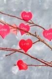 Les coeurs rouges avec un amour d'inscription accrochent sur des branches sur un fond concret gris Arbre d'amour Le concept de la Photos stock