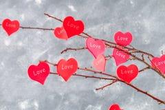 Les coeurs rouges avec un amour d'inscription accrochent sur des branches sur un fond concret gris Arbre d'amour Le concept de la Images stock