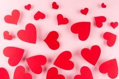 Les coeurs rouges de papier volent sur le fond rose mou de couleur Concept de Saint Valentin pour la conception Photos libres de droits
