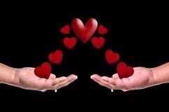 Les coeurs rouges volent dans des mains sur le fond noir Concept d'amour Photos stock