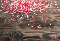 Les coeurs sont dispersés sur une table en bois Photos stock