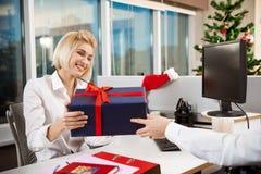 Les collègues célébrant la fête de Noël dans donner de sourire de bureau se présente Photos stock