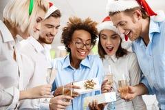 Les collègues célébrant la fête de Noël dans donner de sourire de bureau se présente Image stock