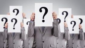 Les collègues d'affaires tenant le point d'interrogation signe devant le thei images stock