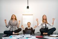 Les collègues méditent dans le bureau sous une ampoule Images stock