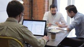 Les collègues s'asseyent à la table et travaillent le chaque avec leur information dans le bureau clips vidéos