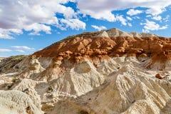 Les collines de bad-lands avec deux ont coloré les couches, le ciel bleu et les nuages Photo libre de droits