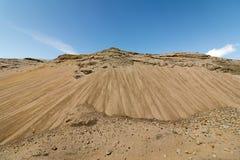 Les collines du sable et de la pierre dans un puits de sable, ciel bleu et nuages blancs, ressemble à une montagne Images stock
