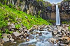 Les colonnes noires de basalte encadrent le jet d'eau Photo stock