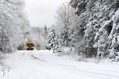 Les commandes d'autobus scolaire sur la neige ont couvert la route rurale Photographie stock