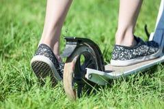 Les commandes d'enfant poussent le scooter comique sur l'herbe verte, se ferment vers le haut de la vue arrière Photo libre de droits