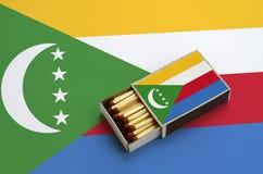 Les Comores diminuent sont montrées dans une boîte d'allumettes ouverte, qui est remplie de matchs et se trouve sur un grand drap photos stock