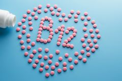 Les comprim?s roses sous forme de B12 au coeur sur un fond bleu, ont d?bord? une bo?te blanche photo libre de droits