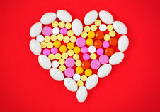 Les comprimés colorés ont arrangé dans une forme de coeur sur le fond rouge Image libre de droits