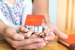 Les concepts, le père et la fille de Chambre tiennent la maison modèle de mains Image libre de droits