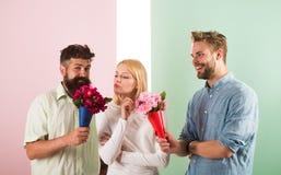 Les concurrents d'hommes avec l'essai de fleurs de bouquets conquièrent la fille La fille aime être dans une attention moyenne La photographie stock