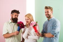 Les concurrents d'hommes avec l'essai de fleurs de bouquets conquièrent la fille La fille aime être dans une attention moyenne Tr Photos stock