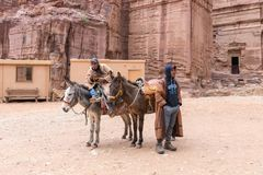 Les conducteurs de bestiaux bédouins se tiennent avec leurs ânes de monte attendant les touristes dans PETRA - la capitale du roy photos stock