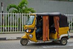 Les conducteurs des tuks jaunes de tuk manient leur commerce habilement autour de ville portuaire Images stock