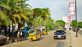 Les conducteurs des tuks jaunes de tuk manient leur commerce habilement autour de ville portuaire Photo stock