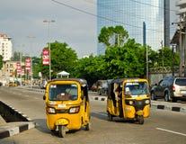 Les conducteurs des tuks jaunes de tuk manient leur commerce habilement autour de ville portuaire Image stock