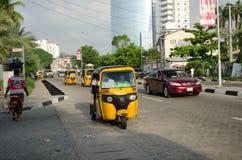 Les conducteurs des tuks jaunes de tuk manient leur commerce habilement autour de ville portuaire Photos libres de droits