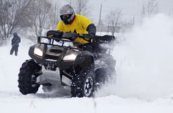 Les conduites de gestionnaire de vélo de quarte au-dessus de la piste de neige Images stock