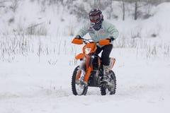Les conduites du gestionnaire du vélo de moto au-dessus de la piste de neige images libres de droits