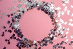 Les confettis en forme d'étoile ont dispersé sur un fond rose C?l?bration et partie, concept Copiez l'espace photographie stock