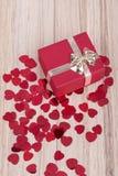 Les confettis rouges de coeurs dans la valentine de boîte aiment le concept Image stock