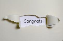 Les congrats de mot apparaissant derrière le papier déchiré Image libre de droits