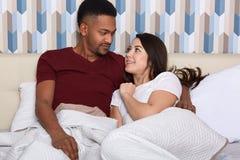 Les conjoints heureux étreignent dans le lit dans le matin, sourire et se caressent La pièce, le lit, les oreillers, le mari et l photo libre de droits