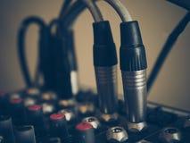 Les connecteurs de microphone pluged dans une console de mélange de musique audio vi Images libres de droits