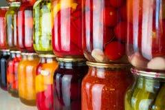 Les conserves de légumes et les ingrédients de nourriture ont placé dans une rangée Images stock
