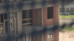 Les constructeurs ayant beaucoup d'étages fonctionnent dans un berceau suspendu sur une façade du bâtiment Plan rapproché clips vidéos