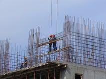 Les constructeurs fonctionnent à un chantier de construction Photographie stock